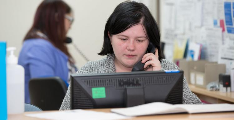 Receptionist on the phone at a GP surgery