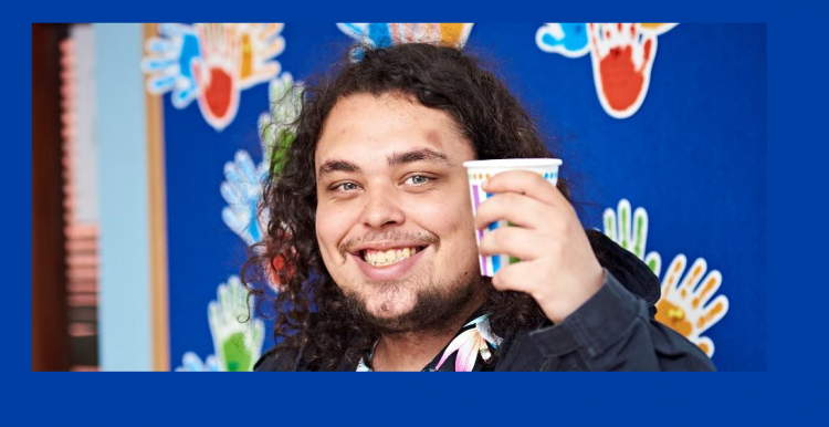 man smiling, drinking a hot drink