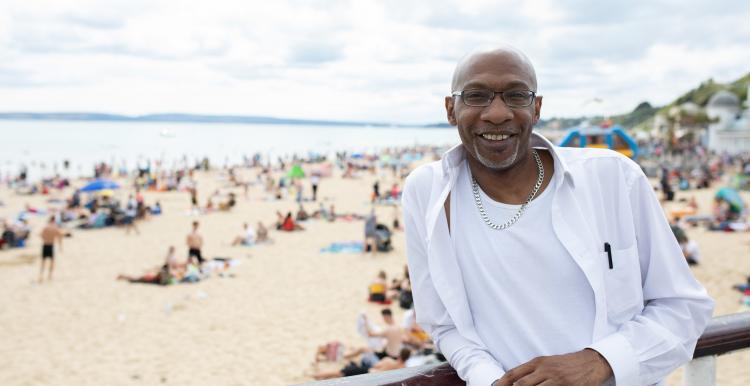 a man with a beach behind him