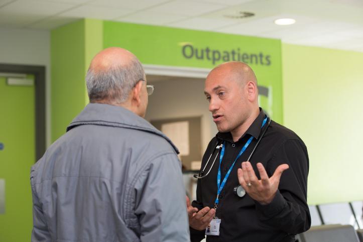 A photo of two men talking inside a hospital corridor