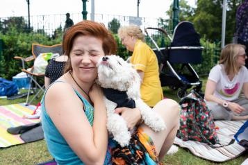 Woman smiling and holding her dog in the park