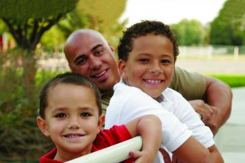 Man smiling with his two young children