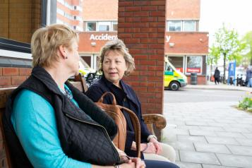 two ladies sit and talk on a bench