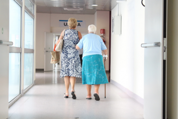 woman assisting an elderly lady in a hospital corridor