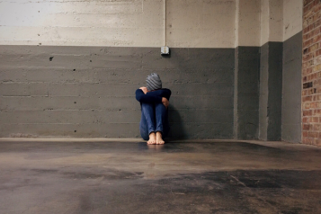 person sitting on the floor, head resting on knees
