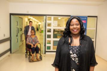 lady standing in a hospital corridor, lady in a wheelchair in the background
