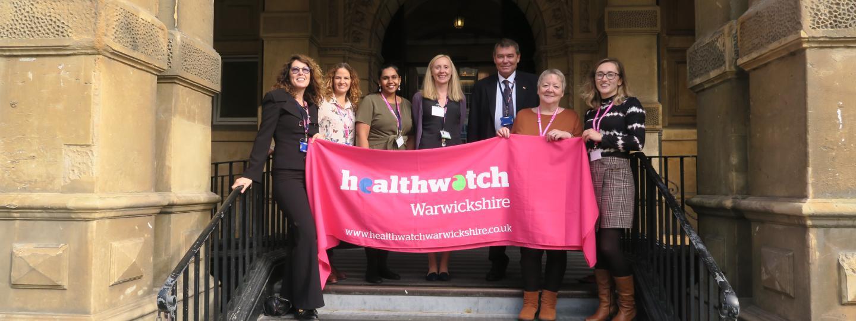 staff team holding a Healthwatch Warwickshire banner
