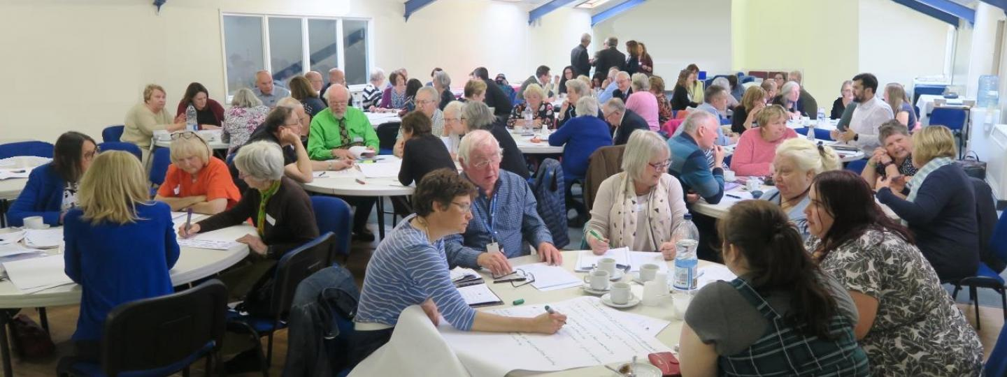 People around tables at a Healthwatch event