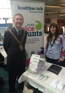 Mayor of Rugby standing with a member of staff at a stall at Rugby Library